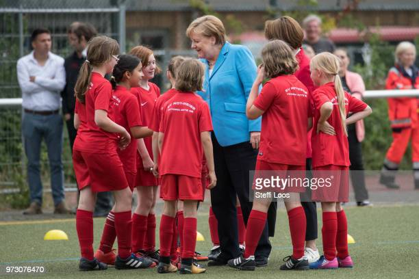 German Chancellor Angela Merkel talkes to young girls during a visit of a program to encourage integration of children with foreign roots through...