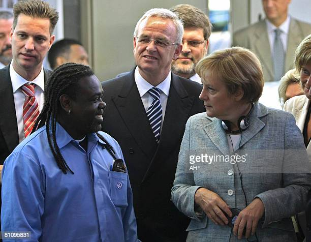 German Chancellor Angela Merkel talks to a worker as she is accompanied by Volkswagen' s CEO Martin Winterkorn and the president for Volkswagen in...