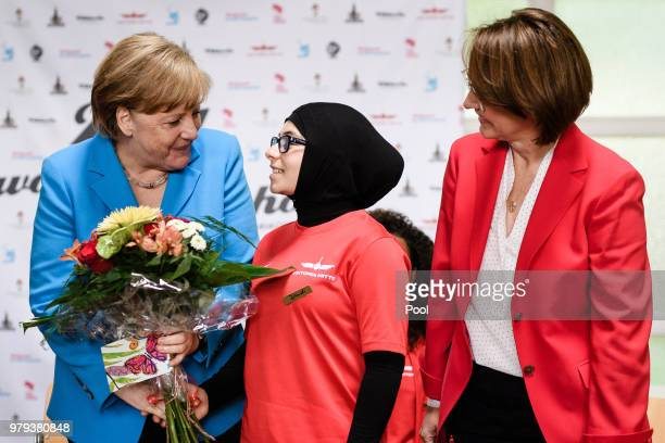 German Chancellor Angela Merkel talks to a young member of the sports club 'SV RotWeiss Viktoria Mitte 08' Joudi who presented her with some flowers...