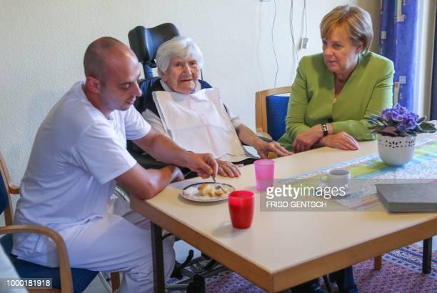 German chancellor Angela Merkel talks to an inhabitant and carer Ferdi Cebi of the retirement home St Johannisstift in Paderborn on July 16 2018 to...