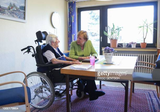 German chancellor Angela Merkel talks to an inhabitant of the retirement home St Johannisstift in Paderborn on July 16 2018 to get an insight in the...