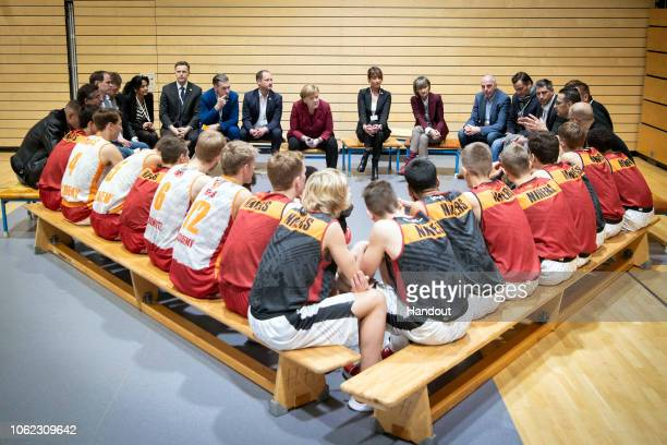 German Chancellor Angela Merkel talks to basketball players from Niners Chemnitz during her visit to the city on November 16 2018 in Chemnitz Germany...