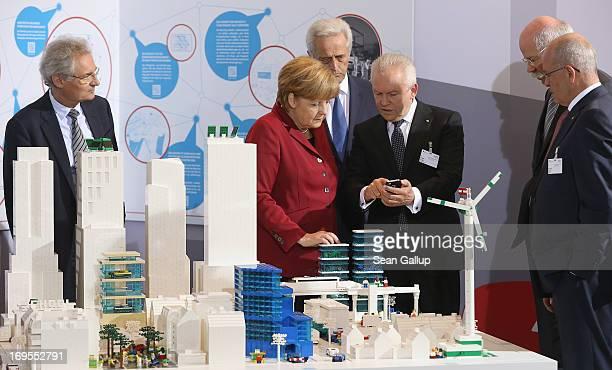German Chancellor Angela Merkel talks to Deutsche Bahn head Ruediger Grube as Transport Minister Peter Ramsauer stands behind and Henning Kagermann...