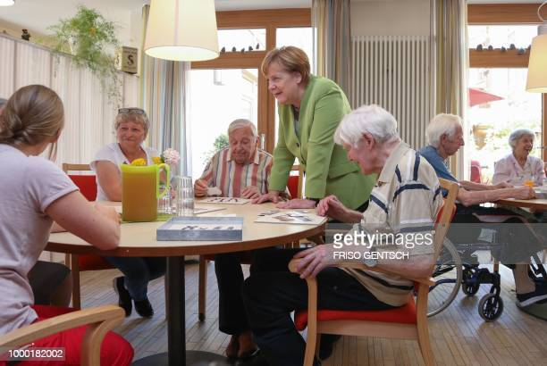 German chancellor Angela Merkel talks to inhabitants of the retirement home St Johannisstift in Paderborn on July 16 2018 to get an insight in the...