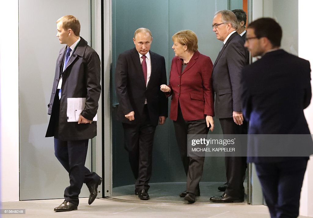 German Chancellor Angela Merkel (3L) talks to Russian President Vladimir Putin at the chancellery on October 19, 2016 in Berlin. German Chancellor Angela Merkel hosts the leaders of Russia, Ukraine and France in a new push for peace in eastern Ukraine. / AFP / POOL / Michael Kappeler