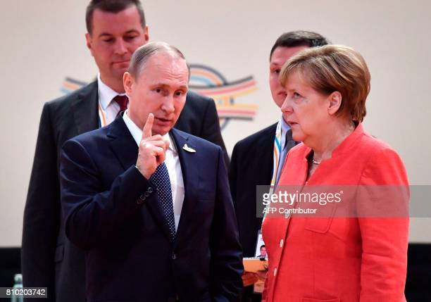 German Chancellor Angela Merkel talks to Russia's President Vladimir Putin at the start of the first working session of the G20 meeting in Hamburg...
