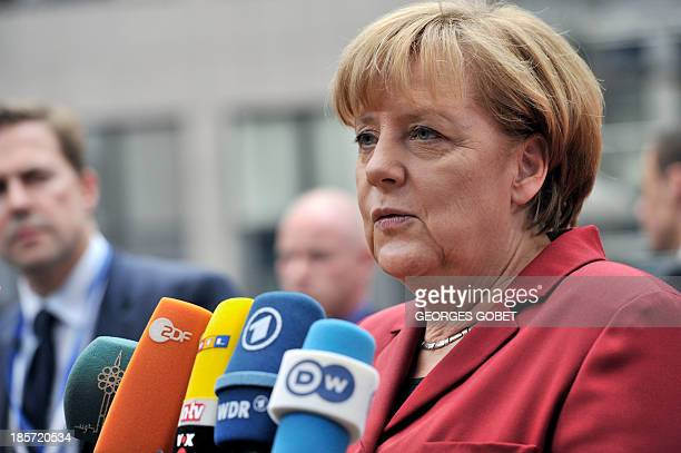 German Chancellor Angela Merkel talks to the press on October 24 2013 upon her arrival to attend a European Council meeting at the EU headquarters in...