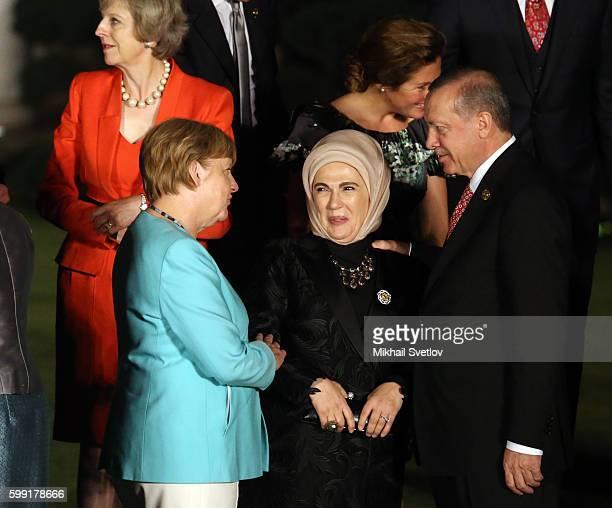German Chancellor Angela Merkel talks to Turkish President Recep Tayip Erdogan as his wife Emine Erdogan seen during a family photo at the G20...