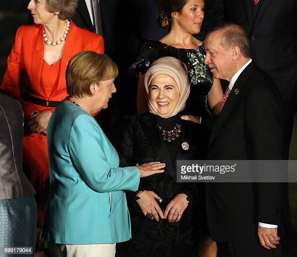 German Chancellor Angela Merkel talks to Turkish President Recep Tayip Erdogan as his wife Emine Erdogan looks on during a family photo at the G20...