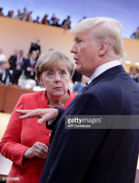 German Chancellor Angela Merkel talks to US President Donald Trump at the start of the first working session of the G20 meeting in Hamburg, northern...