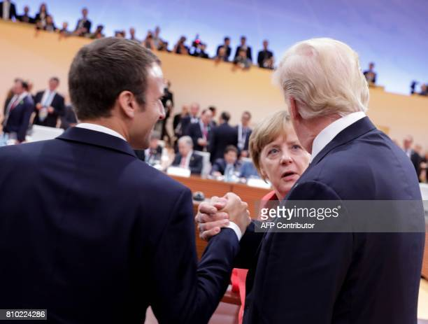 German Chancellor Angela Merkel talks to US President Donald Trump and French President Emmanuel Macron at the start of the first working session of...