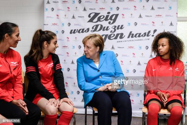 German Chancellor Angela Merkel talks to young members of the sports club 'SV RotWeiss Viktoria Mitte 08' during a visit to the club on June 13 2018...