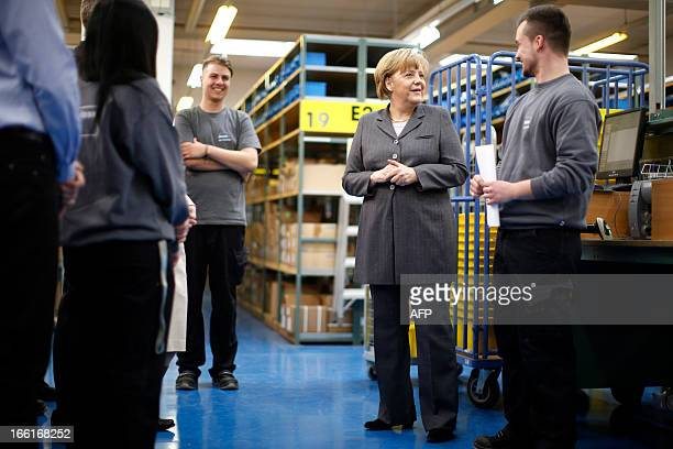 German Chancellor Angela Merkel talks with a trainee during her visit at the pneumatic systems producing company Mader in LeinfeldenEchterdingen...