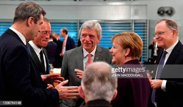 German Chancellor Angela Merkel talks with Bavaria's State Premier Markus Soeder , Hesse's State Premier Volker Bouffier and Lower Saxony's State...