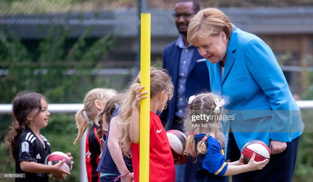 German Chancellor Angela Merkel talks with children as she takes part in the event 'Sports and Integration' as she visits the 'SV Rot-Weiß Viktoria Mitte 08' sports club in Berlin on June 13, 2018, prior to the German government's integration summit. (Photo by Kay Nietfeld / dpa / AFP) / Germany OUT