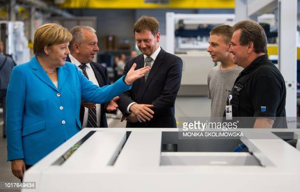 German Chancellor Angela Merkel talks with employees of the Trumpf Sachsen GmbH engineering company in Neukirch near Dresden eastern Germany as she...