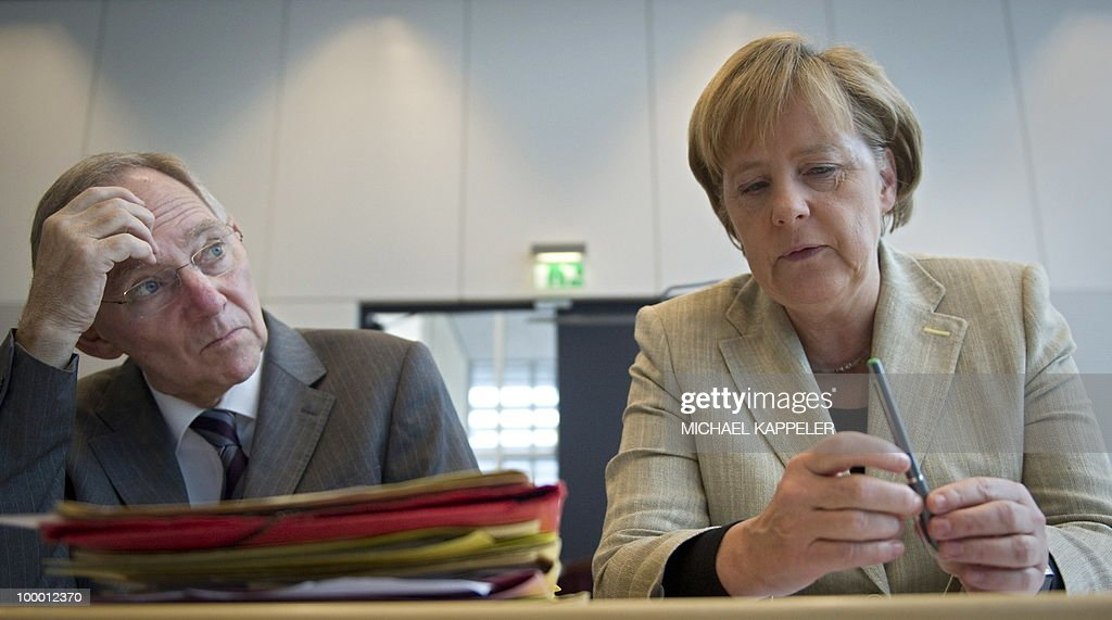 German Chancellor Angela Merkel talks with Finance Minister Wolfgang Schaeuble ahead of a meeting with their conservative CDU party's parliamentary group on May 20, 2010 in Berlin. Merkel said during a conference on financial regulation she would lead a campaign for a tax on financial markets at the next summit of the Group of 20 major economies in June and called for international support.