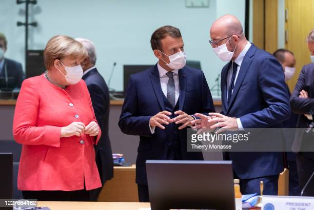 German Chancellor Angela Merkel talks with French President Emmanuel Macron and President of European Council Charles Michel during an EU summit on...