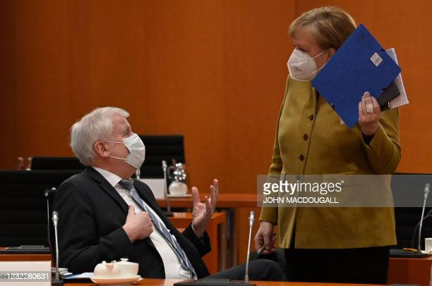 German Chancellor Angela Merkel talks with German Interior Minister Horst Seehofer as she arrives for the weekly cabinet meeting on April 13, 2021 at...