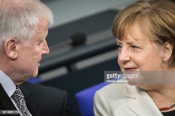 German Chancellor Angela Merkel talks with German Interior Minister Horst Seehofer before the swearingin ceremony of the new federal government on...