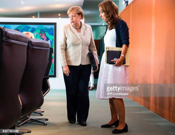 German Chancellor Angela Merkel talks with German State Secretary for Migration Refugees and Integration Aydan Ozoguz prior to the weekly cabinet...