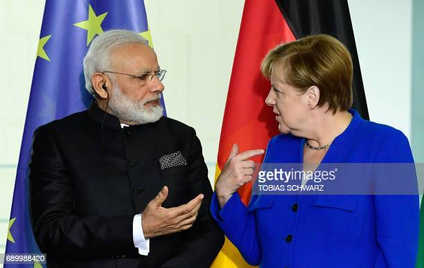 German Chancellor Angela Merkel talks with Indian Prime Minister Narendra Modi as delegation members sign agrreements at the Chancellery in Berlin on...
