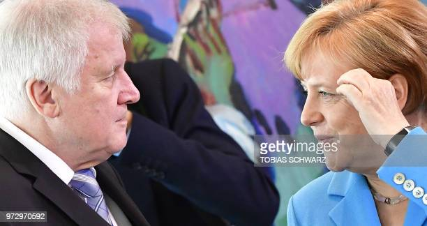 German Chancellor Angela Merkel talks with Interior Minister Horst Seehofer prior to the weekly cabinet meeting in Berlin on June 13 2018