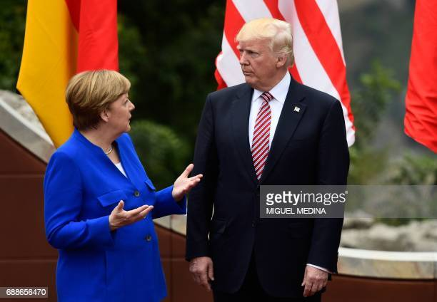 TOPSHOT German Chancellor Angela Merkel talks with US President Donald Trump as they attend the Summit of the Heads of State and of Government of the...