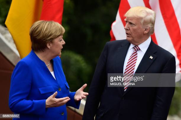 German Chancellor Angela Merkel talks with US President Donald Trump as they attend the Summit of the Heads of State and of Government of the G7 the...