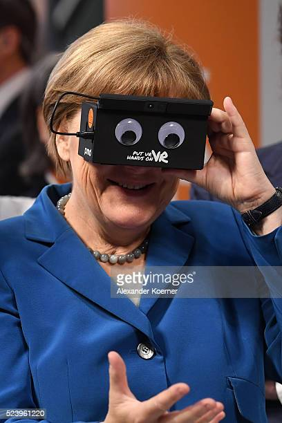 German Chancellor Angela Merkel tests virtual reality glasses at the ifm electronics stand at the Hannover Messe industrial trade fair on April 25...
