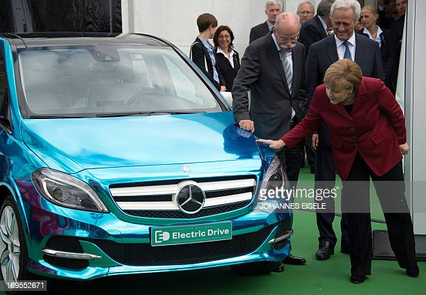 German Chancellor Angela Merkel touches a Mercedes Edrive electric car next to Daimler AG CEO Dieter Zetsche during the Electric Mobility conference...