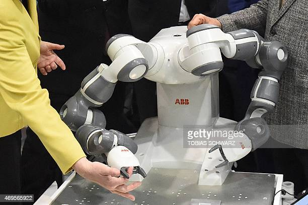German Chancellor Angela Merkel touches the collaborative dualarm robot YuMi next to Indian Prime Minister Narendra Modi at the Swiss automation...