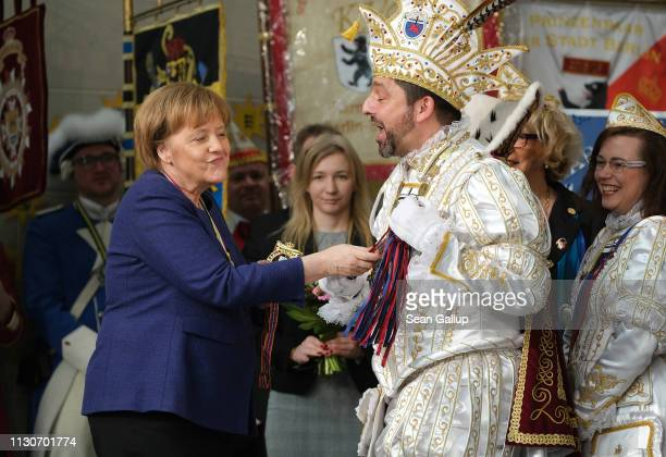 German Chancellor Angela Merkel touches the scepter of a Carnival prince during the annual Carnival reception at the Chancellery on February 19 2019...