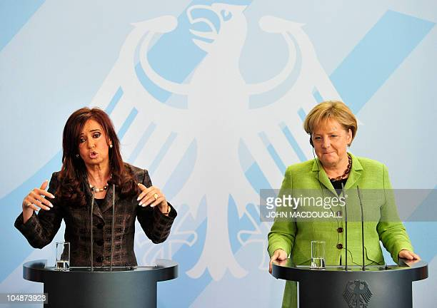German Chancellor Angela Merkel tries not to laugh as she and Argentina's President Cristina Fernandez de Kirchner address a press conference...