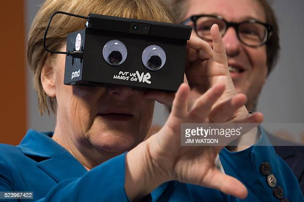 German Chancellor Angela Merkel tries on a pair of virtual reality goggles at the Hannover Messe Trade Fair in Hannover Germany April 25 2016 USA is...