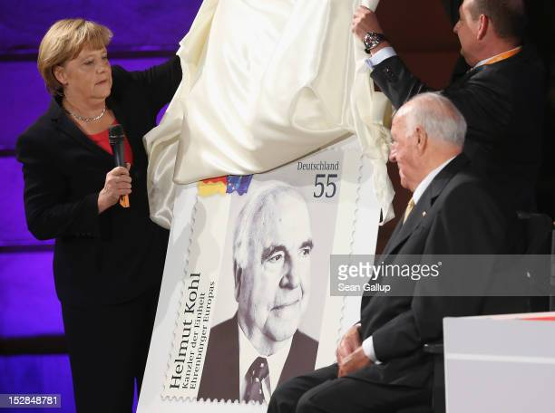 German Chancellor Angela Merkel unveils a commemorative postal stamp showing former German Chancellor Helmut Kohl as Kohl looks on at a gala evening...