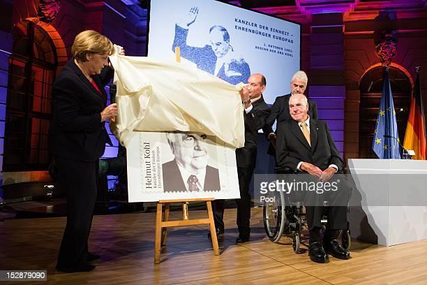 German Chancellor Angela Merkel unveils a commemorative postal stamp showing former German Chancellor Helmut Kohl as the former Chancellor looks on...