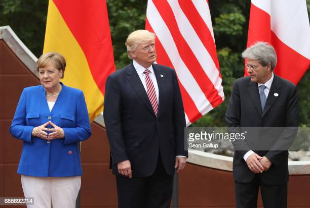 German Chancellor Angela Merkel US President Donald Trump and Italian Prime Minister Paolo Gentiloni arrive for the group photo at the G7 Taormina...