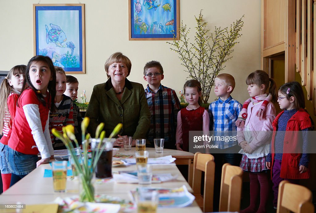 German Chancellor Angela Merkel (C) visits a child day care center on March 13, 2013 in Neumuenster, Germany. According to recent studies Germany is short 200,000 spots for children at child day care centers across the country and local municipalities are wrangling with the federal government for increased funding so they can hire more day care center workers. Germany faces federal elections later this year and the day care center issue is one all the leading political parties are trying to address.