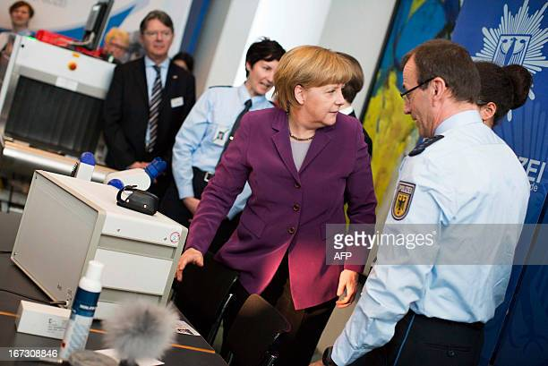 German Chancellor Angela Merkel visits a stand of the German Federal police as part of the Girls' Day at the Chancellery in Berlin on April 24, 2013....