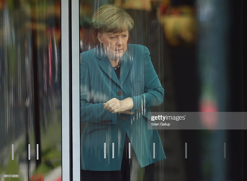 German Chancellor Angela Merkel waits for the arrival of Japanese Prime Minister Shinzo Abe inside a glass door of the Chancellery on April 30, 2014 in Berlin, Germany. The two leaders are meeting on a variety of issues, including the current crisis in eastern Ukraine.
