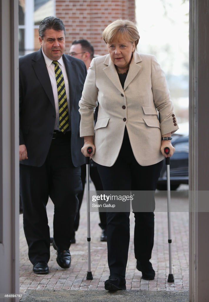German Chancellor Angela Merkel, walking with crutches due to a cross-country skiing injury, and Vice Chancellor and Economy and Energy Minister Sigmar Gabriel arrive to speak to journalists following two days of meetings of the German government cabinet at Schloss Meseberg palace on January 23, 2014 in Meseberg, Germany. The government cabinet of Christian Democrats and Social Democrats was on a two-day retreat at Meseberg.
