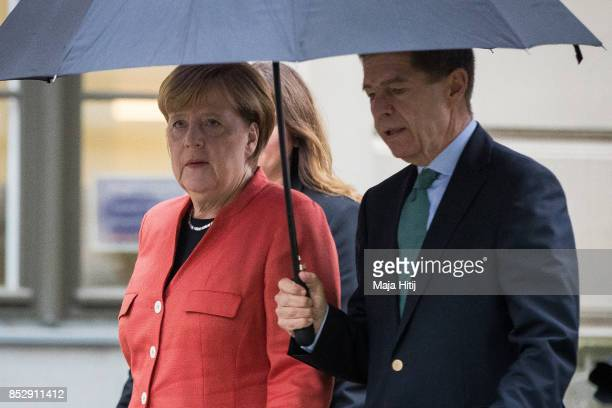 German Chancellor Angela Merkel walks out of the pooling station with her husband Joachim Sauer after she casted her ballot in German federal...