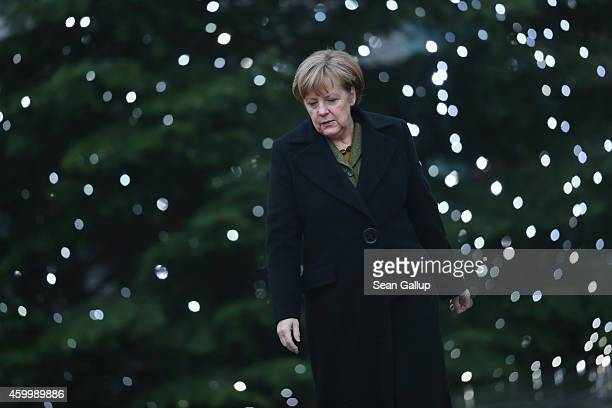 German Chancellor Angela Merkel walks past a Christmas tree with Afghan President Ashraf Ghani upon Ghani's arrival at the Chancellery on December 5,...