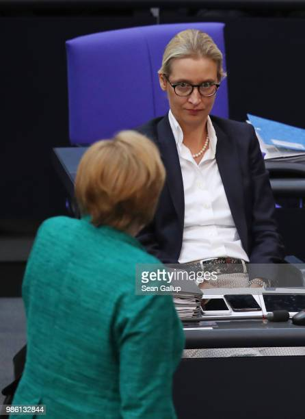 German Chancellor Angela Merkel walks past Alice Weidel of the rightwing Alternative for Germany political party after Merkel gave a government...