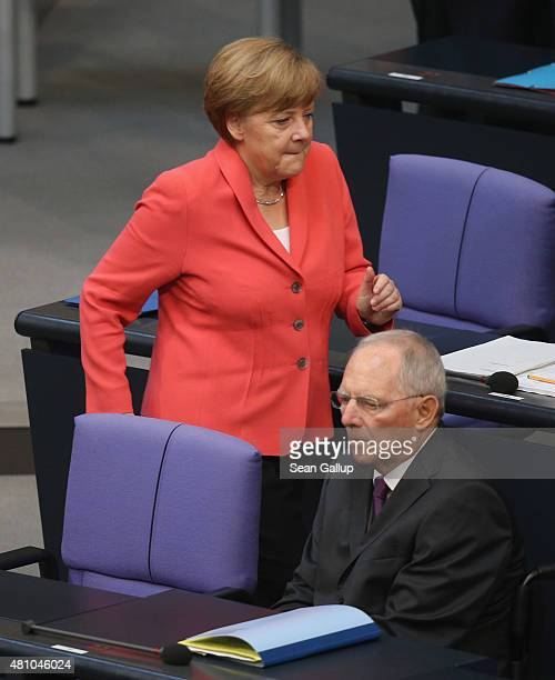 German Chancellor Angela Merkel walks past Finance Minister Wolfgang Schaeuble as she arrives for debates prior to a vote over the third EU financial...