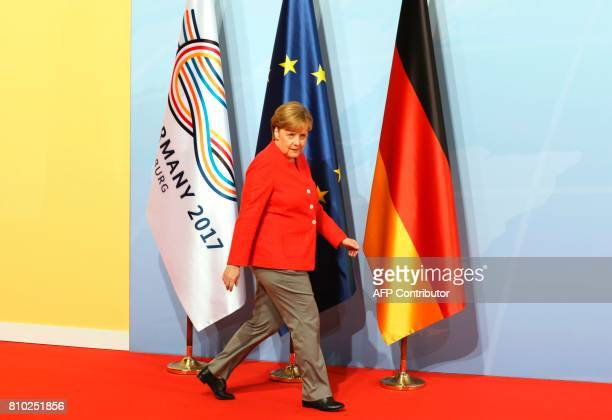 German Chancellor Angela Merkel walks past flags as she arrives before greeting heads of State at the start of the G20 meeting in Hamburg northern...