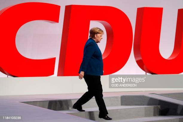 German Chancellor Angela Merkel walks past her party's logo at the end of a party congress of Germany's Christian Democratic Union on November 23,...