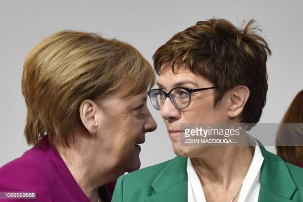 TOPSHOT German Chancellor Angela Merkel walks past her successor newly elected leader of the Germany's conservative Christian Democratic Union party...