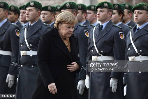 German Chancellor Angela Merkel walks past the honor guard, prior to the arrival of Libya's Prime Minister Fayez al-Sarrajwalk at the Chancellery in...
